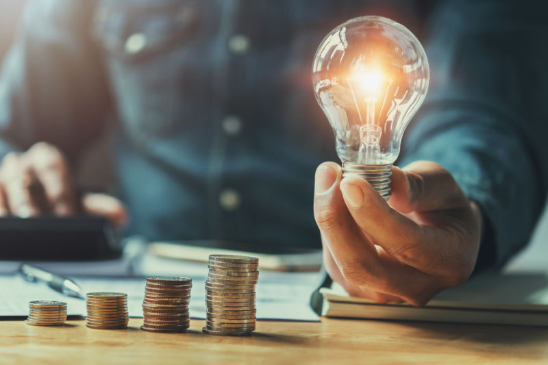 man holding a lightbulb with a stack of coins nearby.