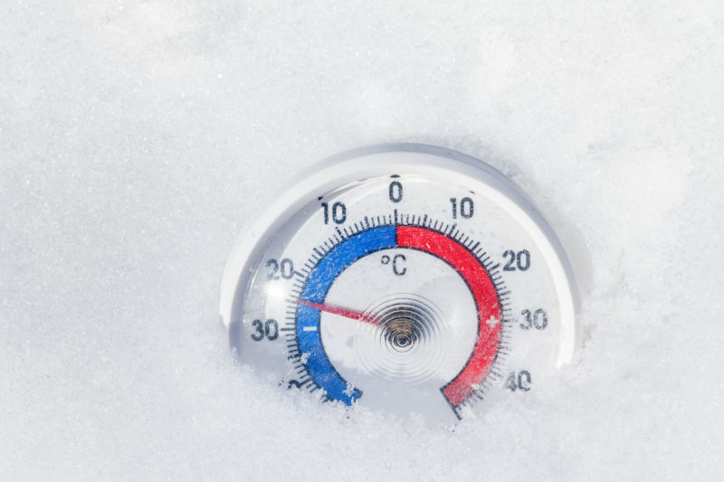 Thermometer with celsius scale placed in a fresh snow showing sub-zero temperature minus 25 degree - cold frosty winter weather concept