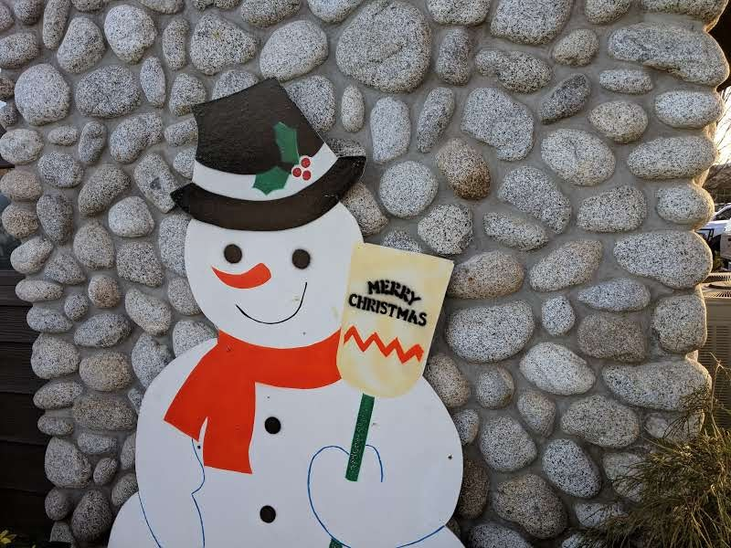 Snow man holding a sign that says Happy Holidays